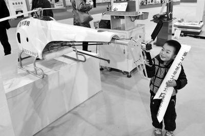 安徽工业设计大赛作品展上,一个孩子被一架无人机吸引。